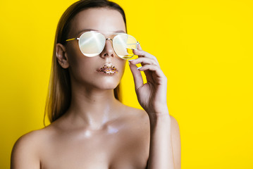 beautiful blond girl with glasses on a yellow background. place for advertising