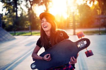 Cute urban girl holding skateboard in skatepark - hipster style photo