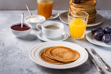 Pancakes with honey, fruit and coffee on a gray background