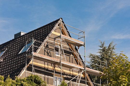 Ein Baugerüst am Giebel eines Hauses mit Spitzdach