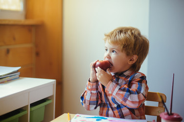 Boy eats apple, looks up and paints picture. Happy healthy baby in kindergarten or at home. Creativity and snack. Healthy breakfast, lunch or dinner with fresh fruit