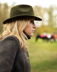 woman in hunting hat with horses in background