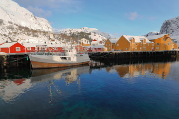 Snow covered harbor-Nusfjord fishing village-wooden fishing boat moored. Flakstadoya-Lofoten-Norway. 0485