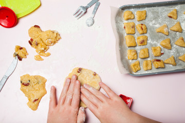 Children's hands prepare delicious cookies with berries, the top view. Toy dishes, the concept of homemade cakes.