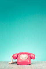 Retro aged telephone on wooden table front mint green wall background. Vintage old style filtered photo