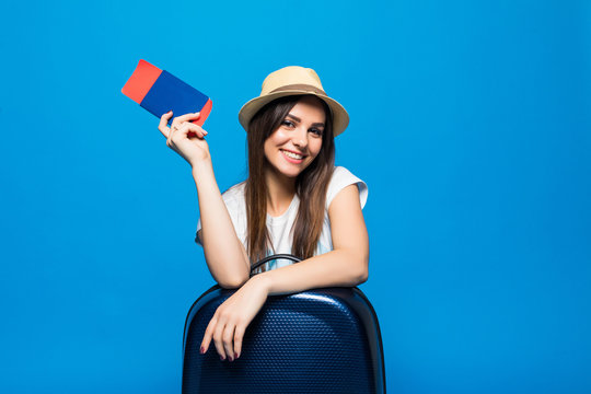 Young woman with blue suitcase and ticket passport on blue background