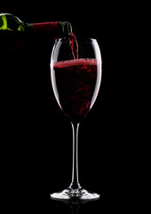 Pouring red wine from bottle to glass on black