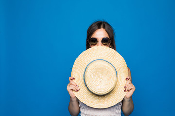 Portrait of cute woman covering face with round hat on blue background