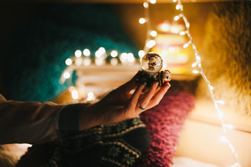 Christmas mood. Woman holding a snowglobe with new year bulbs in background.