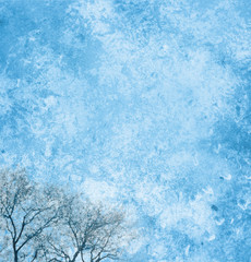 Background page design for a photo book, scrapbook or wallpaper in sky blue; abstract stone textures with winter trees
