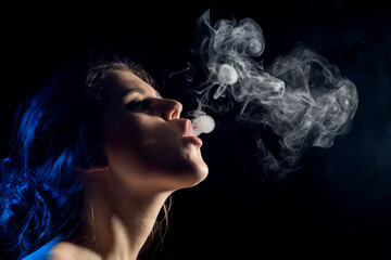 young woman with clouds of smoke smoking on black background