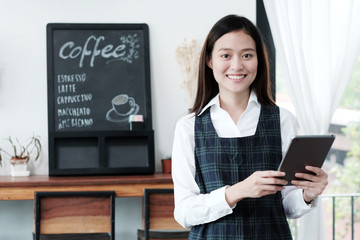Young asian woman, barista, using tablet at cafe  background, food and drink concept