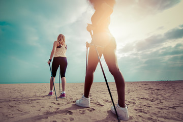 two girls nordic walking with sticks on beach. low angle back view. cyan to orange color sun flare effect Wall mural