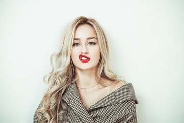 Blonde woman with long hair standing against white wall making face expressions