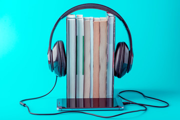 Phone with black headphones with a stack of books on a blue background. Concept of audiobooks and modern education