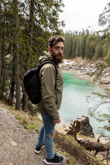 Hipster Adventurer hikes along Lake Obernberg in the mountains of Austria