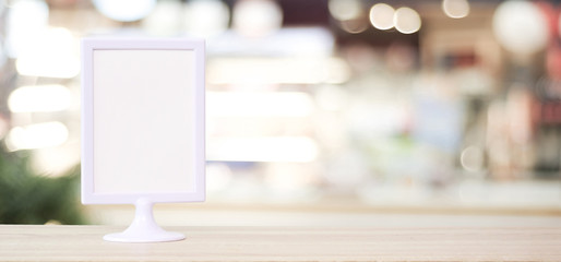 Blank white menu board standing on wood table over blur restaurant with bokeh background, space for text, mock up, product display montage, banner