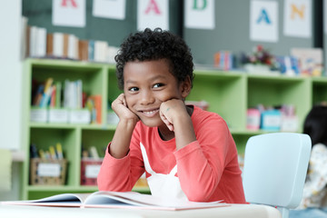 African boy sitting at his desk with smiling face in pre-elementary classroom, kindergarten, pre school education concept