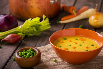 vegetable soup shot on wood boards at an angle with copper pot loose carrots celery onions peas with a spoon landscape