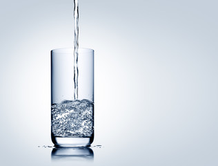 Water pouring and splashing into half full, half empty glass with reflection on blue grey background