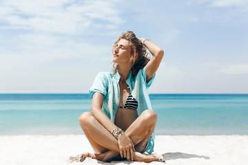 beautiful young cheerful woman in bikini sitting on the beach