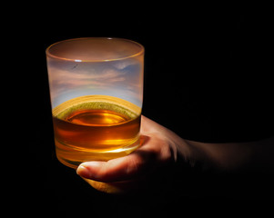 glass of whiskey with a setting sunset inside