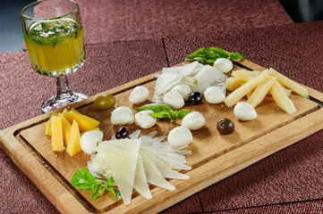 Assortment of cheese on a rustic cutting board wooden background.