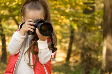 little girl is holding a camera and taking a photo. hobby.