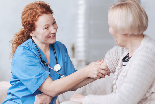 Positive minded nurse taking care of elderly woman at home