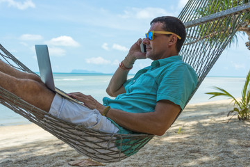 Young caucasian man in a hammock on the beach using a laptop and talking on the phone