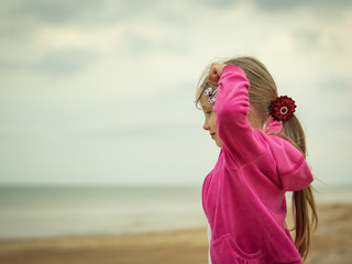 The girl keeps a good mood in bad weather near the cold sea.