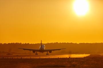Tuinposter Ferien Urlaub Reise Flugzeug landet Flughafen Sonne Sonnenuntergang