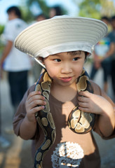 Yong cute asian boy hold snake on his shoulder.