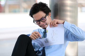 Exhausted young Asian business man tearing up charts or paperwork.