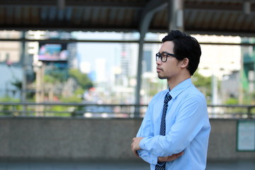 Portrait of confident young Asian businessman looking far away at outside office. Business vision concept.