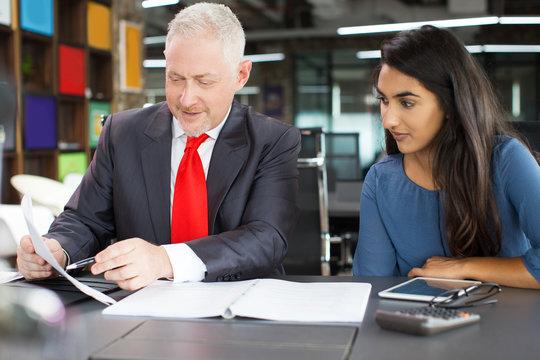 Serious senior businessman with female apprentice