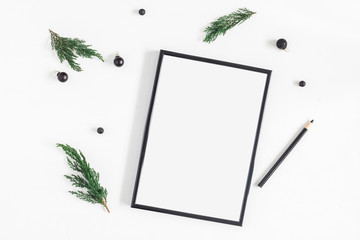 Christmas composition. Black frame and christmas tree branches on white background. Flat lay, top view, copy space