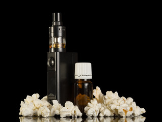 Electronic device for smoking and fragrant liquid, near popcorn isolated on black background