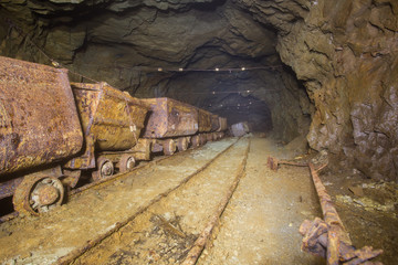 Underground mine shaft gold copper ore tunnel gallery with rails and ore carts wagons