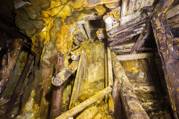 Underground abandoned ore mine shaft tunnel gallery with collapsed ore chutes