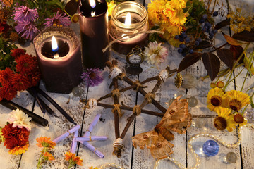 Wooden pentagram with moth, black candles and flowers on planks