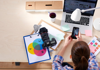Female photographer sitting on the desk with laptop . Female photographer
