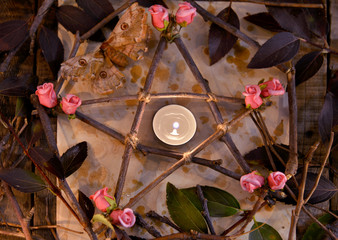 Wooden pentagram with leaves, flowers and candle on paper, top view