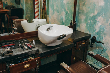 Workplace with a washbasin in barbershop. Interior of luxury beauty salon.