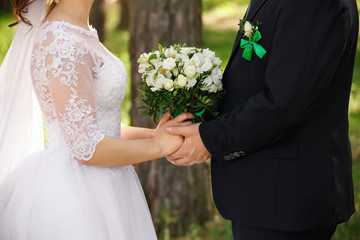 Wedding couple with bouquet of fresh flowers, bride and groom holding hands, newlyweds in love after wedding ceremony