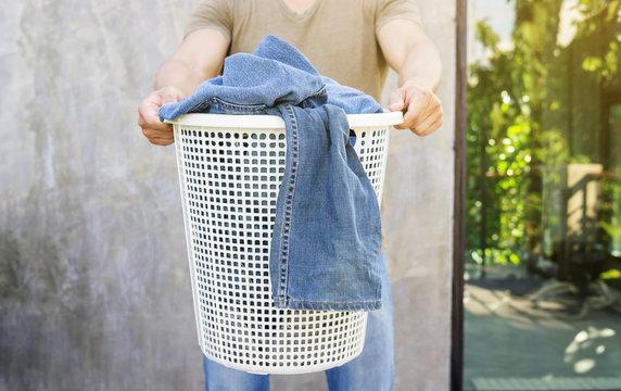 Man holding a white laundry hamper.