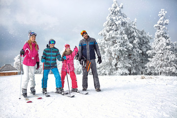 Skiing family enjoying winter vacation on snow in sunny cold day in mountains