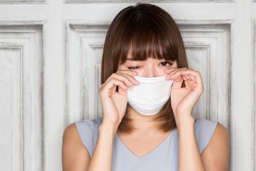 マスク・眼をこする女性