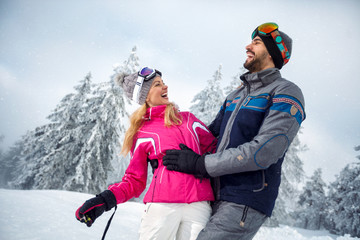 young couple having fun on winter vacation on the mountain