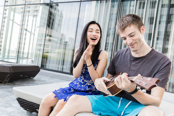 couple of caucasian and asian lover play fun with happiness and joyful and ukulele song outdoor location